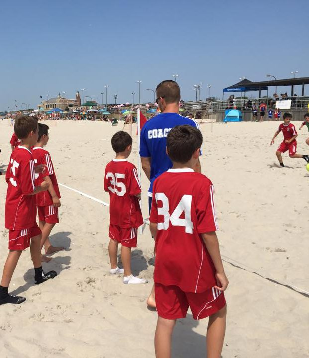 Trainer-Coaching der Fußballspieler auf einem Beach Soccer Feld